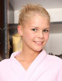 Young teenage girl enjoys playing with small pink dildos